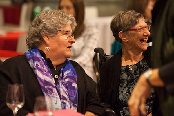 Mary Lou and Denise seated at a table and laughing.