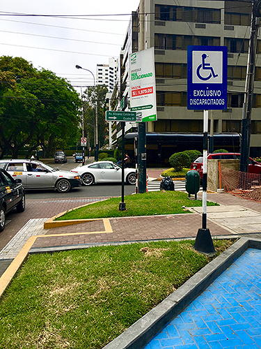 Blue parking spot with blue wheelchair sign and curb cuts in the sidewalk.