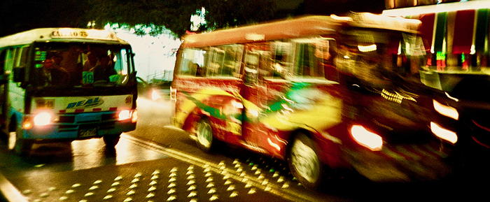 Two small busses on the street at night.