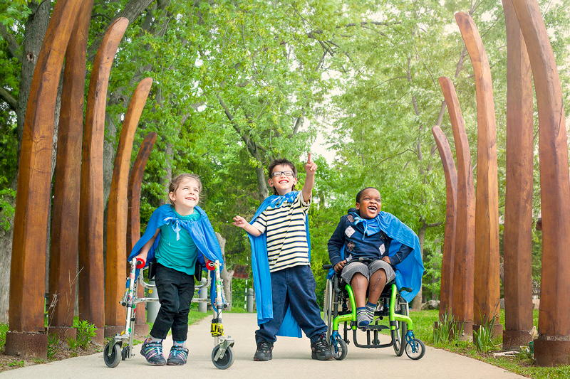 3 children, one using a wheelchair, another a walker, wearing capes and playing in a wooded area.