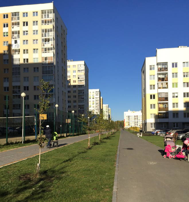 People pushing baby strollers on pedestrian paths with green space amid high rise apartment buildings on a sunny day.