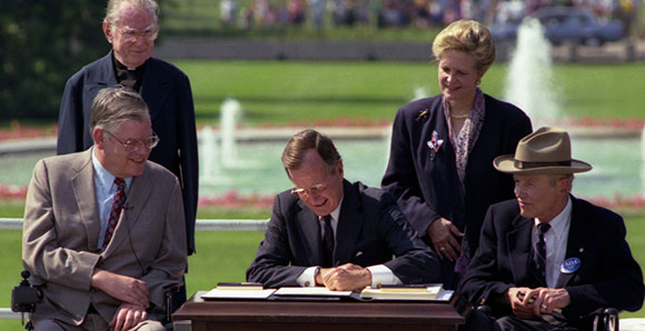 George H.W. Bush signing the ADA into law at the signing ceremony in 1990
