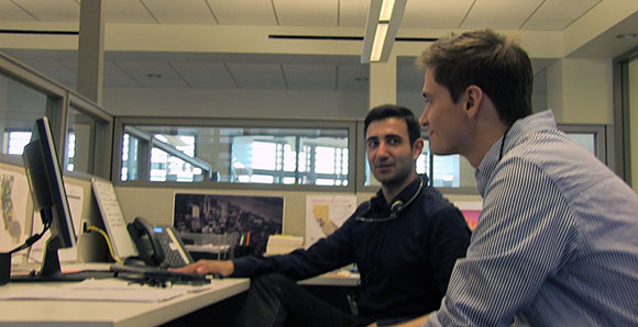 Two young men chatting at a workstation in the DREDF offices.