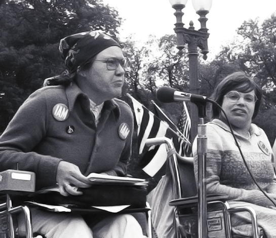 Kitty Cone speaking into a microphone at the demonstration. Judy Heumann is next to her on stage.