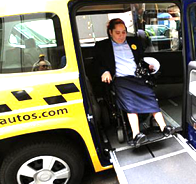 Wheelchair user exiting accessible taxi.