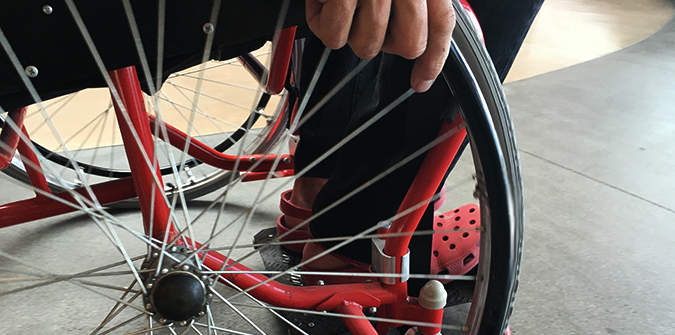Close-up of the wheel of a wheelchair and wheelchair user's hand.