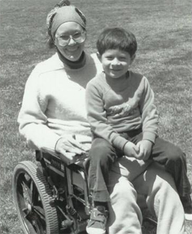 Kitty seated in wheelchair on lawn with child in her lap