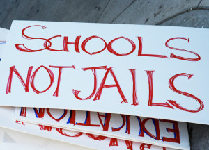 "Protest sign on the ground reads ""Schools Not Jail"""
