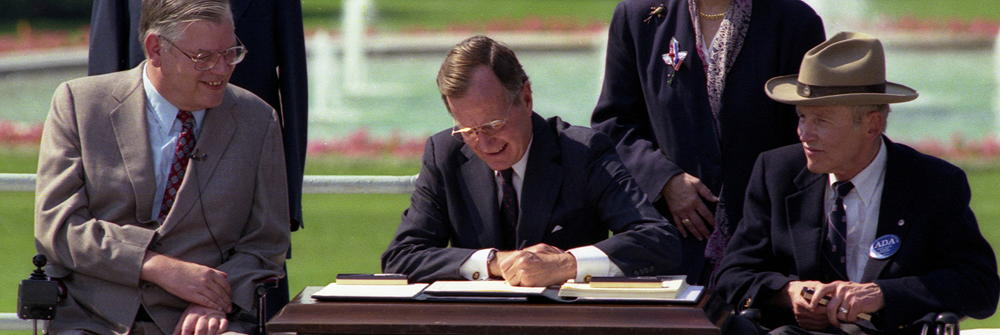 George H.W. Bush signing the ADA into law at the signing ceremony. Justin Dart is seated to his left
