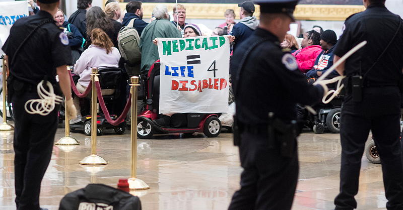 Adapt protesters holding sign that reads Medicaid = Life for Disabled. Police in foreground.