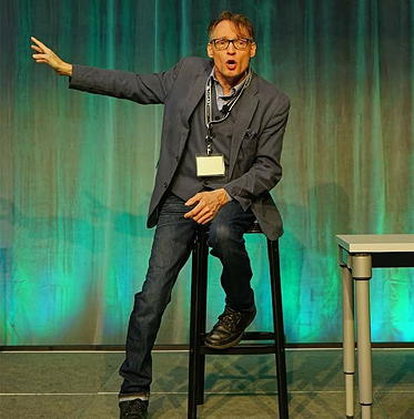 Lawrence Carter-Long sitting on a stool giving a talk at a conference.