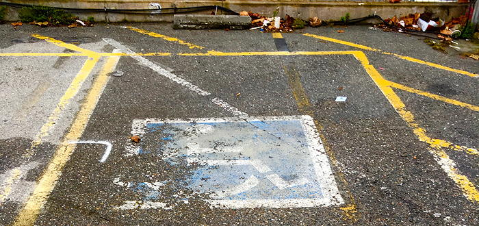 A deteriorated, barely recognizable handicap parking symbol