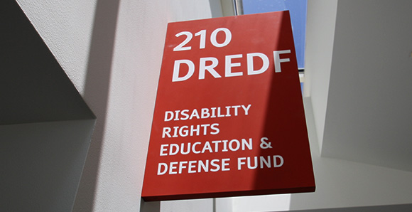 Sign at DREDF's office reads: 210 DREDF Disability Rights Education and Defense Fund